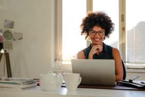 Portrait of smiling young woman sitting at her desk with laptop. African female sitting at a table with laptop looking at camera and smiling in office.