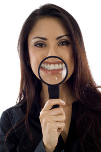 pretty woman magnifying her smile